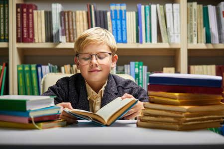 preschooler little boy reading a book in the library, little caucasian boy reading a book in the library, near a bookcase Archivio Fotografico