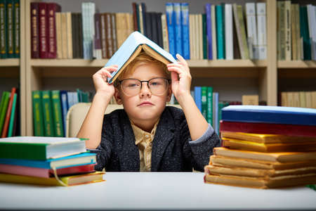 bored little boy tired of learning doing homework reading book, studying preparing for exam test, literature research, children education concept