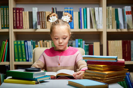 little girl sits with books at table in library,child in bookstore, surrounded by colorful books for school Archivio Fotografico