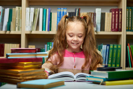 school girl reading book while preparing for lesson in library, diligent and shy child is concentrated on reading