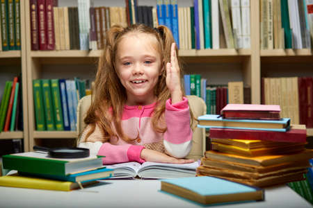 child girl raises her hand, knows the answers to all questions, erudite girl in library. education concept