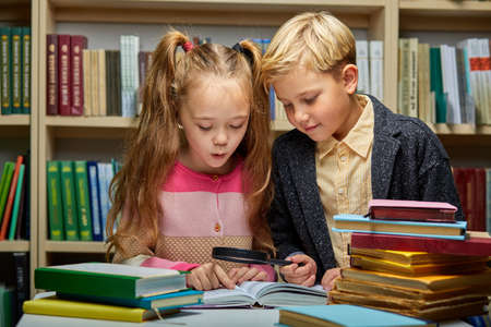 school kids reading book together while sitting at table in library, boy and girl among lots of books, preparing fro school Archivio Fotografico