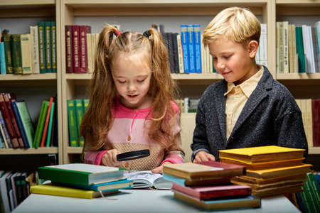 children reading book together while sitting at table in library, boy and girl among lots of books, preparing fro school Archivio Fotografico