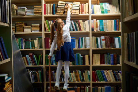 rear view on child girl taking a book from bookshelves in library, choosing. girl in formal school suit uniform