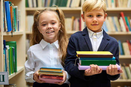 two kids prepared for school, they stand holding stack of books in hands, looking at camera, wearing schools outfit Archivio Fotografico