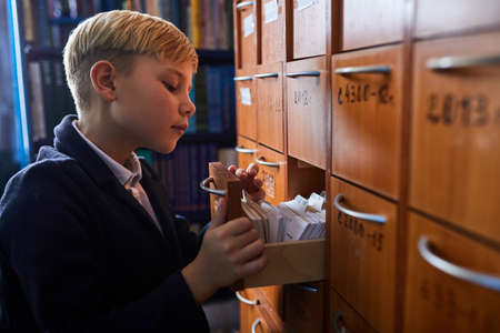 kid boy in search of his library card, opening shelves, looking for his one. in school library