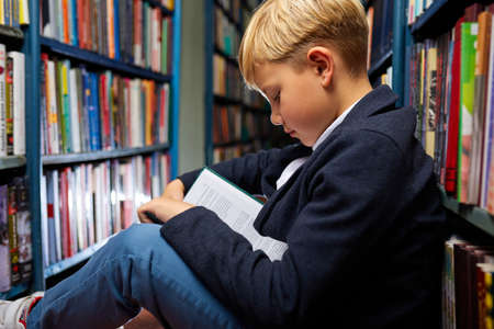 boy is sitting in a book store and read book, education and school concept. in library
