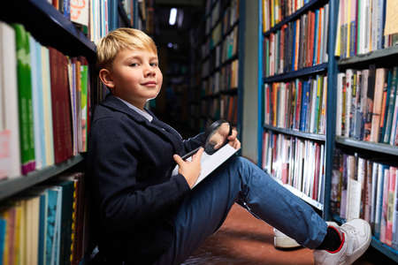 boy carefully reads every word in book using a magnifying glass, while sitting on the floor between the shelves in library Archivio Fotografico