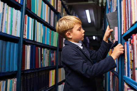 boy in school wear pulls out one book he wants to take from the library, get knowldge. education concept Archivio Fotografico
