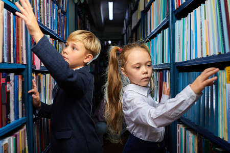 kids boy and girl choose books in library for school, going to read, get knowledge