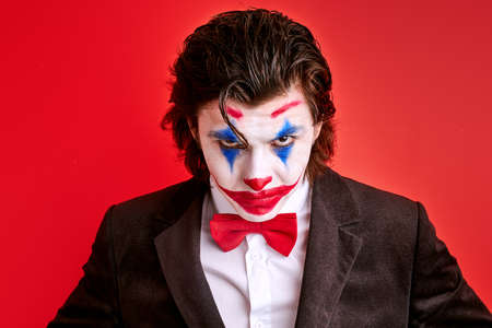 portrait of virile harsh illusionist with colourful make-up confidently looking at camera, magician in suit isolated over red background