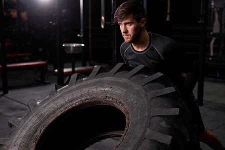 Fit male athlete doing tire-flip exercise indoors in modern gym. Cross fit and workout. Strong and handsome athlete in sportswear. sport, healthy lifestyle