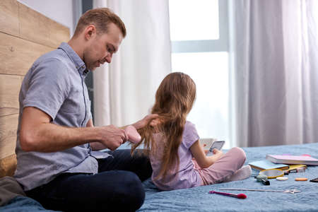 father makes haircut for his daughter by using comb at home on bed, handsome caucasian man sit caring her child girl. indoors Archivio Fotografico