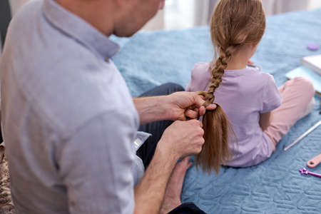 side profile photo father making braids to little girl in morning at home sitting on bed in domestic wear. family relationships, father day concept. close-up Archivio Fotografico