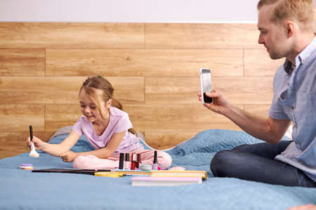 young dad make video on mobile phone showing how his daughter doing make-up, using decorative cosmetics. child girl sit on bed having fun, young little blogger spend time with daddy at home