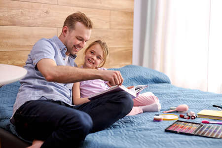 father and daughter spend time reading book at weekends, lovely child girl enjoy spending time with father, smiling. education, homework, family concept