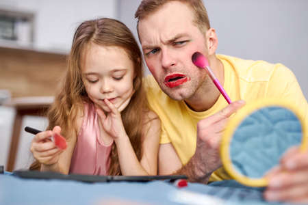 daddy and daughter doing makeup together, little daughter using decorative cosmetics, having fun playing enjoying time with parent at home at weekends. man looking at mirror with confusion