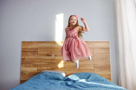 little caucasian child girl in motion jumping on bed alone flying in air feeling joy, cheerful cute active kid in pink dress having fun playing laughing in bedroom after waking up, holiday concept.