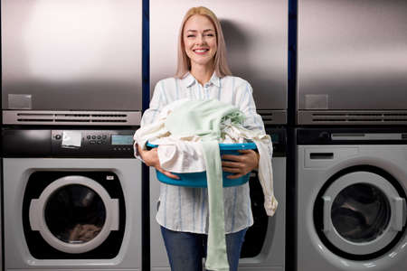 young woman doing laundry at laundromat, looks at camera smiling, holding clothes in hands and standing near washing machines. washing, cleaning, launder, housewife concept
