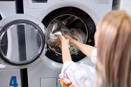 Young female getting out clean clothes from washing machine, people lifestyle concept. cleaning, washing