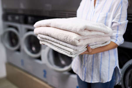 cropped woman is holding a stack of white towels. female in washing house. concept of service in hotels, laundry, spa Archivio Fotografico
