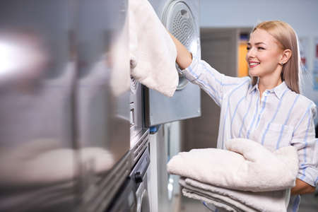 woman doing laundry - putting out white garments towels from washing machine, in washing house