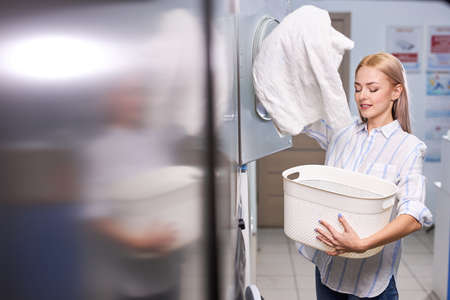 Woman getting towels form washing machine, feeling softness of linen and freshness of washing, enjoying time of cleaning.