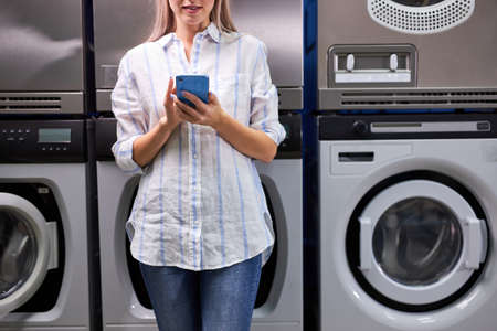 Woman stands next to the washing machine using mobile phone, waiting end of washing. cropped unrecognizable female in washing house