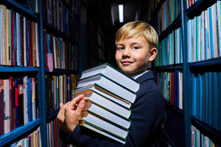 clever kid boy with stack of books in hands preapring fro school, in library, in school wear