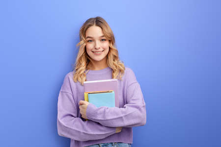 Cheerful beautiful teen student girl hold books isolated on pastel blue background studio portrait