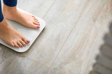 Unrecognizabble female stepping on floor scales indoors, space for text. Overweight problem Stock fotó