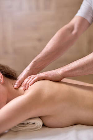 Back massage for young female in modern spa salon. Muscle recovery after exercise. Wellness. Back treatment. sports massage. Standard-Bild