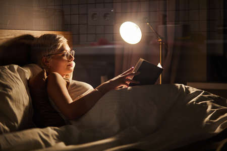 Beautiful female in pajamas and eyeglasses lying on bed reading book, alone at night. Caucasian short haired lady in bedroom, charming cute woman in room lighted by lamp Archivio Fotografico