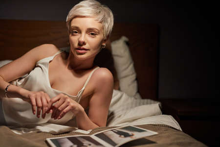 Portrait Of Stylish Lady Lying On Bed Alone, With Magazines Photos On Bed. Elegant Woman Of Caucasian Appearance Having Rest