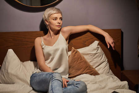 Tired female sit on bed alone having unhappy facial expression, stressed woman in casual wear in bedroom lighted by lamp, worried about something, looking at side