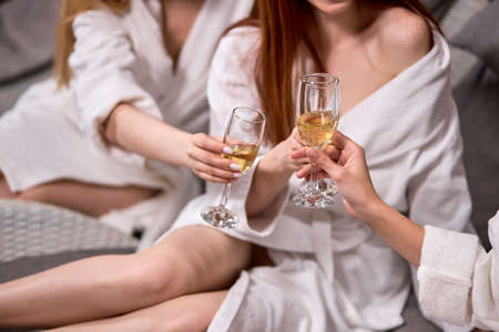 Unrecognizable ladies clinking glasses of champagne while celebrating at spa. Women holding alcohol drinks, champagne in hands, toasting, having rest. close-up hands