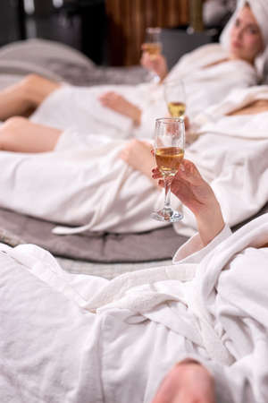 Cropped ladies in bathrobes drinking champagne after spa procedures. Spa hotel vacation concept. Cropped photo of females holding glasses. Focus on hands Archivio Fotografico