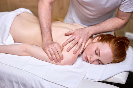 Cropped male masseur doing massage on redhead woman body in spa salon. Beauty treatment concept. Side view on shirtless female lying on stomach Archivio Fotografico