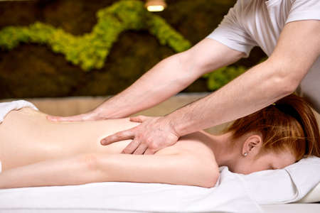 unrecognizable female getting massage on spine, skin care, spa concept, massage, relax. in modern spa center, body therapy Archivio Fotografico