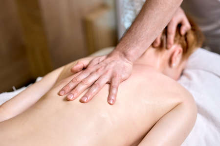 Redhead lady lying on stomach at spa, getting massage on neck and back by professional male masseur. indoors, at spa center