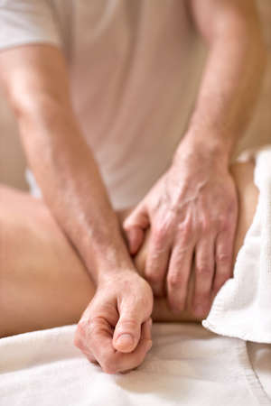 Female enjoying back and spine massage in spa. Focus on Male Masseur hands. Close-up. Professional massage therapist treating female patient. Relaxation,beauty,body and face treatment concept