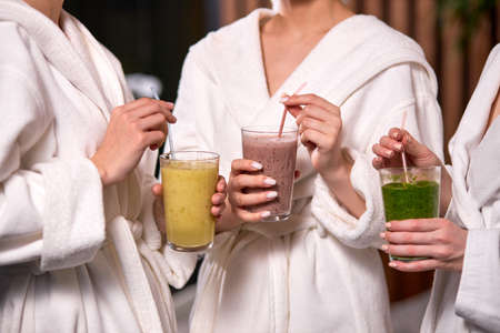 Cropped three women enjoy drinking healthy beverage during spa treatment wearing bathrobes, drinking freshly squeezed juice while spending weekend in wellness center.
