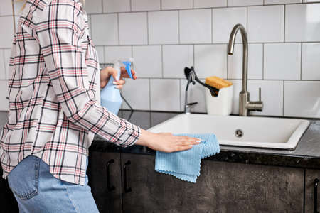 Housewife cleaning the kitchen table and sink with clot blue rag, unrecognizable female in casual wear housekeeping alone at home, side view, cropped photo
