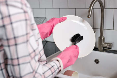 Close-up photo of female hands in pink rubber gloves washing dinner plate with dish brush. Unrecognizable woman in protective gloves doing general cleaning of house