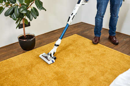 Cropped man cleaning floor carpet with vacuum cleaner in modern white living room. Concept of easy cleaning with vacuum cleaner