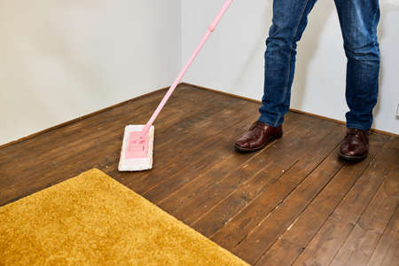 Cropped male housekeeper cleaning floor holding mop in living room house floor helping his wife, removing dirt and dust, at home