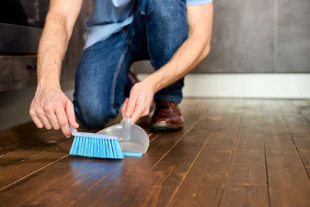 Man Sweeping Dust With Broom On Dustpan, Housekeeping Concept, Close-up Photo. Focus On Blue Broom For Cleaning