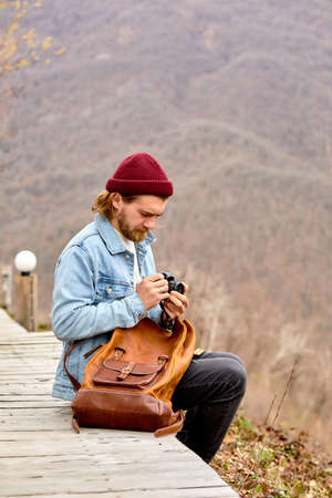 Man travel photographer blogger with camera sit configuring camera, going to take photo of mountains. Travel freelancer lifestyle hobby concept adventure summer voyage outdoor Standard-Bild
