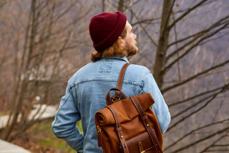 hipster traveler man enjoying natural surroundings, stand in contemplation. Man in denim jacket with leather brown backpack is walking alone outdoors, looking at side. view from back
