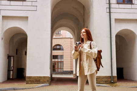 Young caucasian woman with retro camera in hands looking at urban old architecture, taking pictures, discover new places, walking alone in city. Nice female with long natural red hair enjoy trip